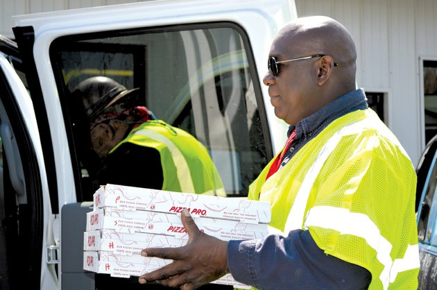 an-employee-of-united-states-environmental-carries-some-of-the-20-pizzas-the-company-ordered-monday-from-yogo-city-in-a-mayflower-shopping-center-the-company-also-bought-30-footlong-sandwiches-from-subway-oil-spill-cleanup-crews-have-been-frequenting-restaurants-in-the-center-boosting-business-managers-said