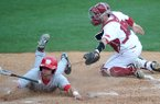 New Mexico baserunner Chase Harris dives home past the tag of Arkansas catcher Jake Wise to score a run in the first game of Tuesday afternoon's doubleheader at Baum Stadium in Fayetteville.
