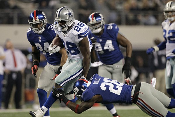 Dallas Cowboys running back Felix Jones (28) escapes a tackle attempt by New York Giants free safety Antrel Rolle (26) as Deon Grant (34) and Mathias Kiwanuka (94) look on during an NFL football game Sunday, Dec. 11, 2011, in Arlington, Texas. The Giants won 37-34. (AP Photo/Tony Gutierrez)