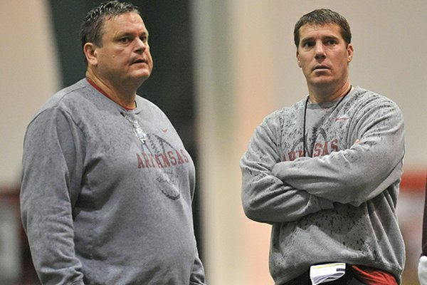 Arkansas assistant coaches Sam Pittman (left) and Chris Ash work with the Razorbacks during practice Saturday morning in Fayetteville.