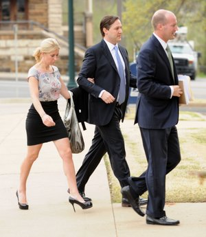 Former developer Brandon Barber, center, is escorted into the John Paul Hammerschmidt Federal Building by associate Kristen Foodim, left, Monday, April 15, 2013, in Fayetteville.