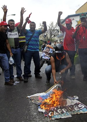 "Government ""Chavista"" supporters burn an election poster of opposition presidential candidate Henrique Capriles in Los Teques, on the outskirts of Caracas, Venezuela, Tuesday, April 16, 2013.  President-elect Nicolas Maduro is blaming Capriles for seven deaths that the government says occurred in post-election unrest. The government has provided names of some people it says have been killed by opposition activists but has provided no evidence. Capriles is demanding a vote-by-vote recount of Sunday's presidential election. (AP Photo/Ariana Cubillos)"