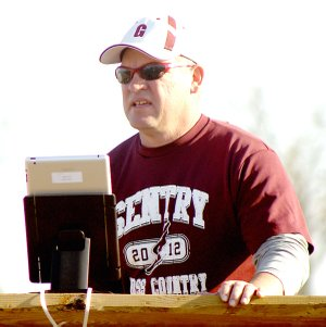 With an iPad mounted on a platform, Gentry coach Daniel Ramsey video records the finish of running events during a track meet last week.