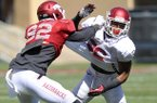 Arkansas players Mekale McKay (left) and Rohan Gaines run drills during the Razorbacks practice Saturday morning at Razorback Stadium in Fayetteville.