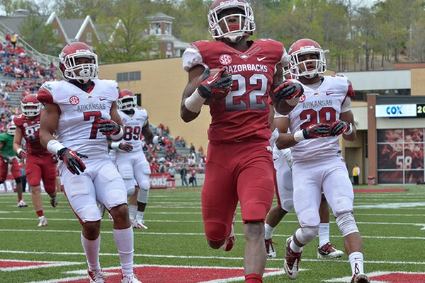 Arkansas running back Nate Holmes beats defenders Tiquention Coleman (left) and Ray Buchanan Jr. to the end zone as he scores a touchdown during the Razorbacks' Red-White scrimmage. Holmes will have a role on the kickoff return team.