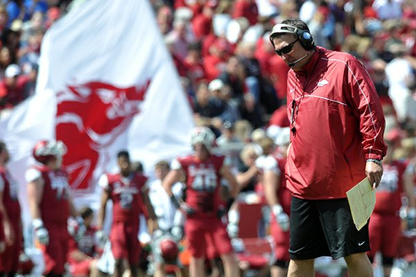 University of Arkansas coach Bret Bielema watches the Razorbacks warm up as they prepare for the start of Saturday's Red White Scrimmage at Razorback Stadium in Fayetteville.