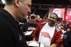 Arkansas football coach Brett Bielema signs autographs for Tim Williams and other fans and supporters during a fund raising program at Verizon Arena in North Little Rock.