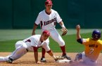 Arkansas shortstop Brett McAfee (center) watches as second baseman Jordan Farris dives to make a force out at second on LSU's Sean McMullen in the top of the third inning on Sunday, April 14, 2013, at Baum Stadium in Fayetteville.