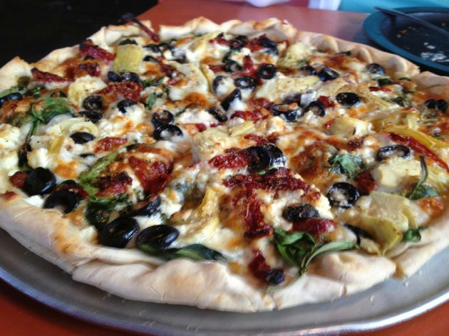 pizza-cafes-mediterranean-pizza-features-mozzarella-feta-sun-dried-tomatoes-artichoke-hearts-spinach-and-black-olives-on-an-olive-oil-base