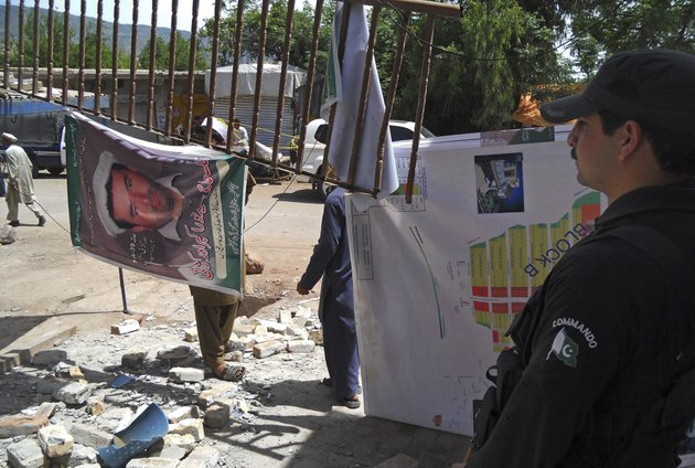 a-pakistani-police-officer-stands-guard-near-an-office-of-a-local-politician-following-a-blast-in-kohat-pakistan-on-sunday-april-28-2013-pakistani-taliban-detonated-bombs-at-the-campaign-offices-of-two-politicians-in-the-countrys-northwest-on-sunday-police-said-killing-many-people-in-an-escalation-of-attacks-on-secular-left-leaning-political-parties