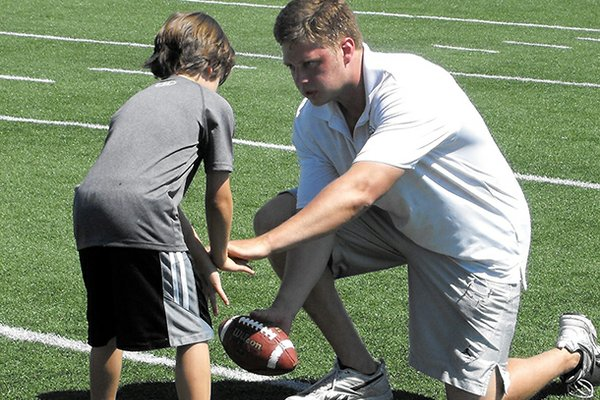 Alex Mortensen works with a youngster during the 2012 NWA Passing Academy in Springdale.