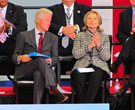 Bill and Hillary Clinton sit on stage during a dedication ceremony for the Little Rock airport named