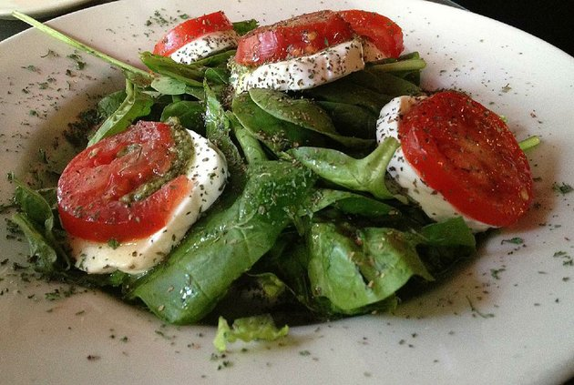 ciaos-vine-ripe-tomato-and-mozzarella-appetizer-comes-on-a-bed-of-spinach-with-pesto-replacing-out-of-season-fresh-basil