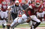 Arkansas quarterback Brandon Mitchell is dragged down by Alabama linebacker Adrian Hubbard during the third quarter of play Saturday, Sept. 15, 2012, at Razorback Stadium in Fayetteville.