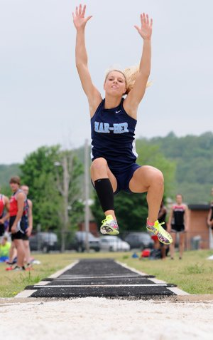 Payton Stumbaugh reaches up high during her long jump attempt Wednesday at the Ramay Junior High School track and field complex in Fayetteville during Day 1 of the decathlon and heptathlon state meets.