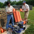 Roy Cordell, left, and Brent Caple, volunteer coaches, load targets on Saturday into a trap, the dev...