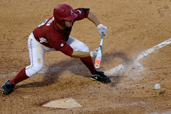 Arkansas' Tyler Spoon lays down a RBI bunt single in the eighth inning of a Southeastern Conference Tournament NCAA college baseball game against LSU at the Hoover Met in Hoover, Ala., Thursday, May 23, 2013. (AP Photo/Dave Martin)