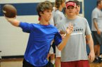 Former Arkansas quarterback and current offensive coordinator for the Tennessee Titans Dowell Loggains works with camper Adam Saveall, 13, of Fayetteville Saturday, Jun. 1, 2013, at Woodland Junior High School in Fayetteville.
