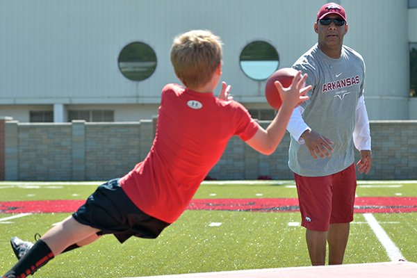 Arkansas receivers coach Michael Smith helps kids work on their diving catches during the University of Arkansas Youth Football Camp.