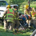 Springdale emergency responders work Tuesday on removing one of the occupants of a Toyota Corolla in...
