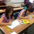 Elizabeth Sanchez, 10, left, and Joselin Villasenor, 12, write vowels Wednesday at J.O. Kelly Middle...