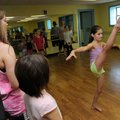 Taylor Rogers, left, instructor, watches Reigan Lutz do kick exercises Thursday during dance camp at...