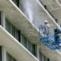 Val Graves with Heartland Painting of Rogers works on a lift Friday as he washes the south side of R...