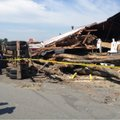 Officials discuss the damage at the Bicycle Doctor in Benton. A truck hauling a load of logs crashed...