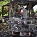 Pakistani volunteers collect body parts of victims of a bomb blast from the wreckage of a bus in Que...