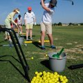 Baylee Maes, right, practices her swing Tuesday at First Tee golf center in Lowell.
