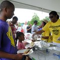 David Wright, 14, left, helps his sister Karyssa Wright, 5, get a hamburger from Charisa Burkhead, r...