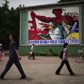 "People walk past a roadside propaganda billboard promoting the ""military first"" policy and a boost t..."