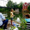 Mia Dence, 7, of Bentonville fishes with her grandparents, Ken (left) and Vicki Mitchell, both of Gr...