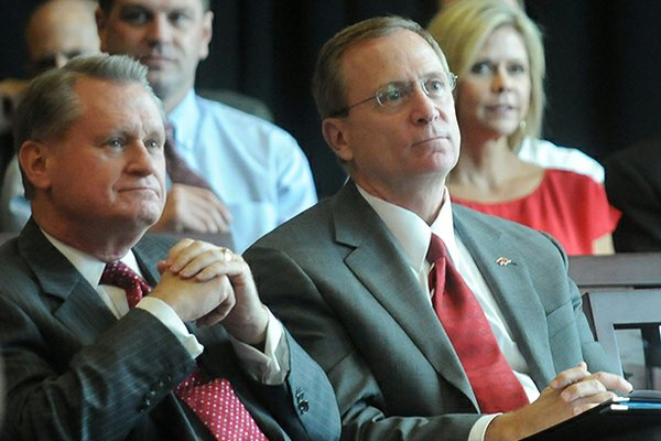 University of Arkansas chancellor David Gearhart (left) and athletics director Jeff Long listen during a Sept. 14, 2012 presentation in Fayetteville.