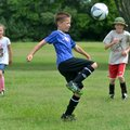 Paolo Shultz, 10, knees the soccer ball as Emerson McElroy, 6, left, and Cole Cash, 8, play a quick ...