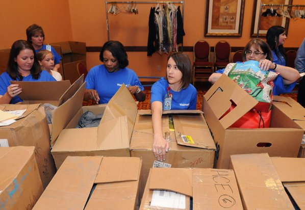 Volunteers from Walmart sort clothing ...