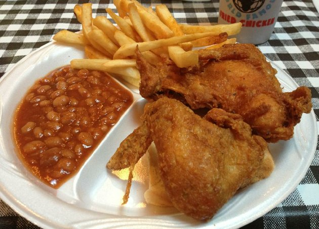a-2-piece-white-plate-with-seasoned-fries-and-baked-beans-at-guss-world-famous-fried-chicken