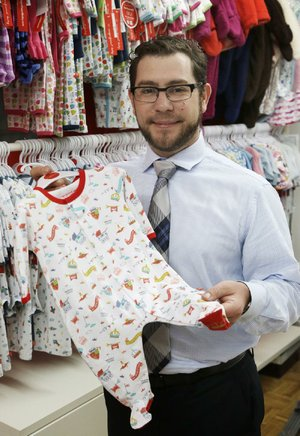 In this Friday, May 31, 2013 photo, Lawrence Scheer displays one of his company's items in their showroom, in New York. Scheer's company, Magnificent Baby, manufactures its products in China and then sells them in about 20 countries around the world. (AP Photo/Mark Lennihan)
