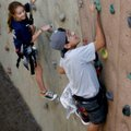 Logan Edge, right, races up the climbing wall Friday against Lelia Wommack, 10, at the Donald W. Rey...