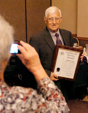 Dodie Evan's wife, Louise, takes a photo of him after he was awarded a plaque at the Arkansas Press Association Convention, honoring him for 60 years of service in the newspaper industry