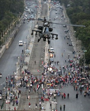 "A military attack helicopter flies over a street near the presidential palace, in Cairo, Egypt, Friday, July 5, 2013. The top leader of Egypt's Muslim Brotherhood has vowed to restore ousted President Mohammed Morsi to office, saying Egyptians will not accept ""military rule"" for another day. General Guide Mohammed Badie, a revered figure among the Brotherhood's followers, spoke Friday before a crowd of tens of thousands of Morsi supporters in Cairo. A military helicopter circled low overhead. (AP Photo/Hassan Ammar)"