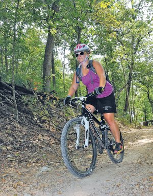 Courtney Walbe takes a spin Saturday along the Slaughter Pen Trail in Bentonville. The mountain bike and hiking trail features a network of loops from easy to difficult.