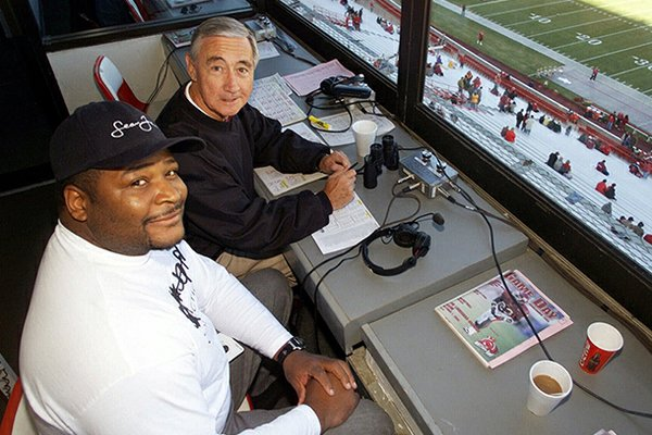 Keith Jackson, left, and Paul Eells pose in the broadcast booth at Razorback Stadium in Fayetteville, Ark., on Saturday, Oct. 7, 2000. (AP Photo/Danny Johnston, File)