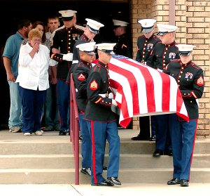 Marines carry the casket of U.S. Marine Corps Lance Cpl. Benjamin Tuttle from the church following Thursday's funeral service at First Baptist Church in Gentry. Tuttle's grandmother and adoptive mother, Faye Tuttle, weeps as she is escorted by Marine Sgt. Cheek, of Tulsa, Okla.