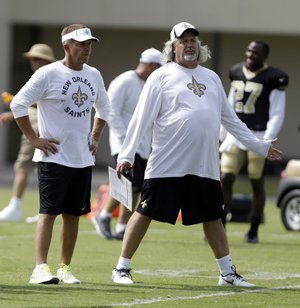 FILE - In this July 30, 2013, file photo, New Orleans Saints head coach Sean Payton and defensive coordinator Rob Ryan chat during NFL football training camp in Metairie, La. Saints defensive players are praising their new defensive coordinator not just for his aggressive, fun-loving approach, but also for his genuine interest in players' opinions about what works best for them. (AP Photo/Gerald Herbert, File)