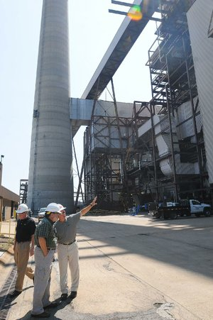 Plant Manager Carl Handley, right, describes the Flint Creek Power Plant in Gentry for several visitors during a 2012 plant tour. The Flint Creek plant is one of three coal-fired stations in Arkansas that are improving their environmental controls to reduce emissions.