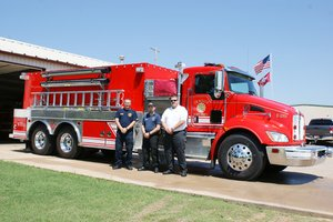 Gravette firefighters, from the left, Robert Douthit and Spencer Gillming, and Fire Chief David Smith stand in front of the new combo pumper/tanker the department received from the county last week. Transfer of hoses, tools, etc., from the two trucks the new rig is replacing has been completed.