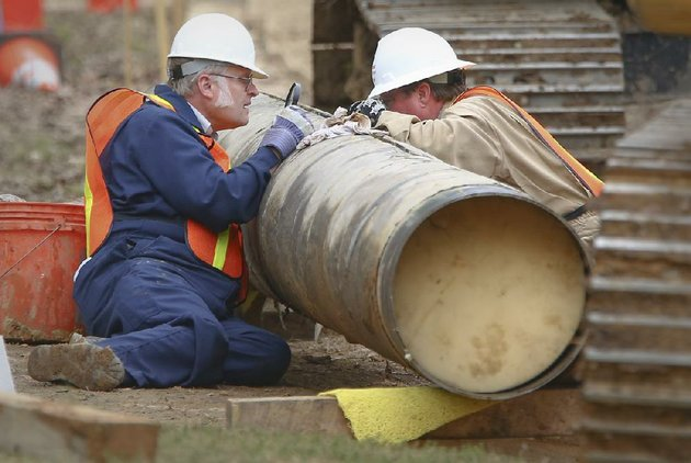 file-exxon-mobil-pipeline-workers-inspect-a-split-in-a-section-of-the-pegasus-pipeline-in-mayflower-on-april-15
