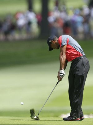 Tiger Woods hits from the fairway on the 13th hole during the final round of the PGA Championship golf tournament at Oak Hill Country Club, Sunday, Aug. 11, 2013, in Pittsford, N.Y. (AP Photo/Julio Cortez)