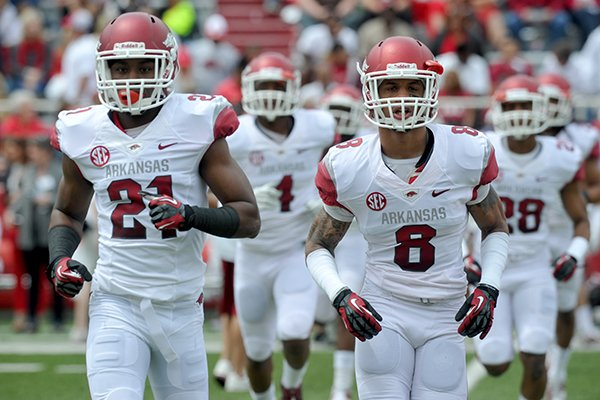 Arkansas cornerbacks Carroll Washington (21) and Tevin Mitchel (8) run onto the field at Razorback Stadium prior to the Razorbacks' Red-White Game on April 20, 2013.